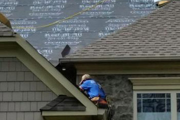 man laying roofing